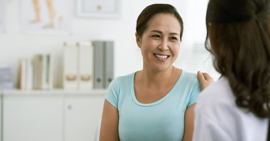 Asian woman being reassured by doctor or nurse