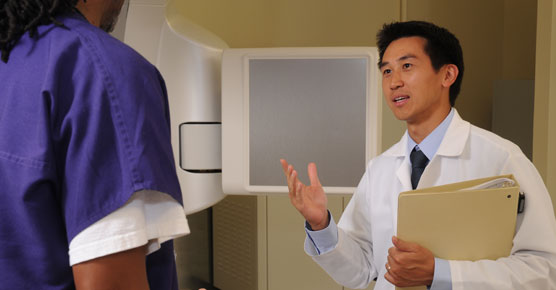 Stanley Liauw, MD, talking with staff member in radiation oncology suite