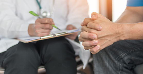 Male patient clasping hands, doctor taking notes