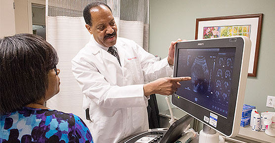 Dr. Nathaniel Crump reviewing a scan with a patient