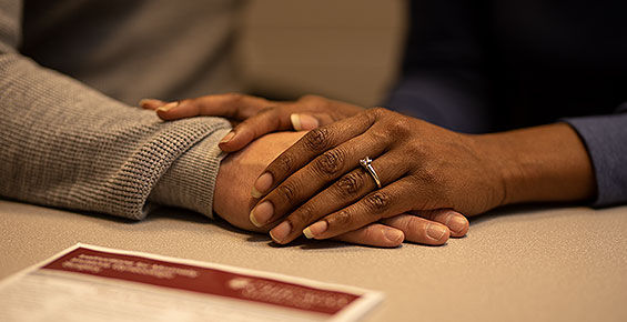Couples' hands on desk with a patient letter nearby