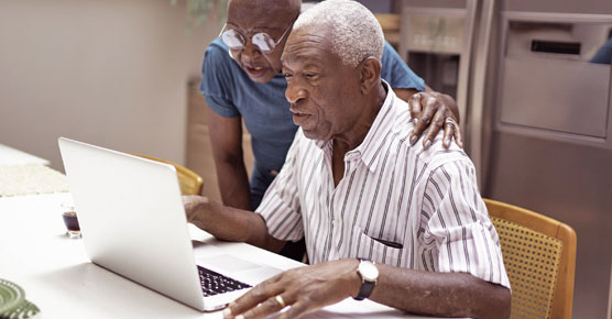 older man and woman at home, looking at laptop screen