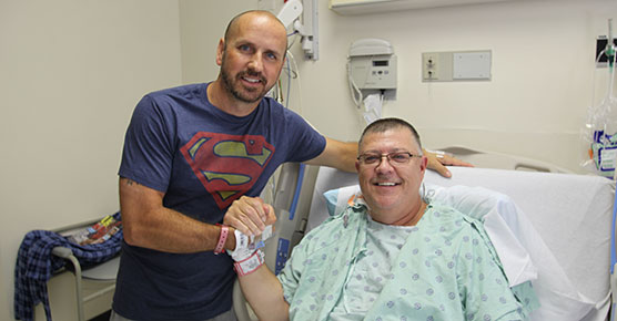 Kidney transplant patient Stewart Botsford (in bed) and his donor, Justin Maduena, visit with each other in Mitchell Hospital after their surgeries two days earlier on August 18, 2016, at University of Chicago Medicine