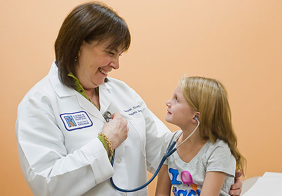 Pediatric surgeon Deborah Leoff, MD, showing a patient a sthethoscope