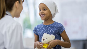Pediatric cancer care, girl with head scarf talking to doctor