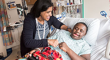 Dr. Neethi Pinto fist bumps a young patient in the PICU