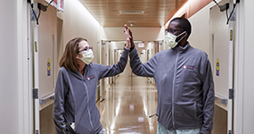 Triple-organ transplant patients, Sarah and Daru, high five each other