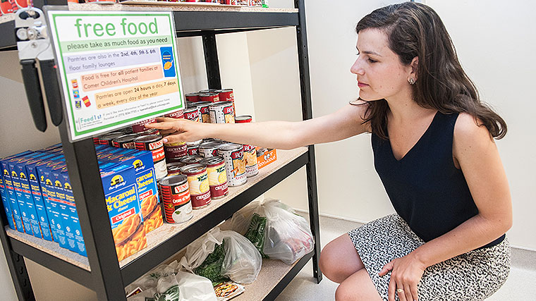 A medical student stocks shelves in the Feed1st food pantry for patients and families