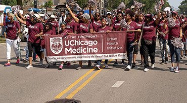 Staff, family members and friends march with the UChicago Medicine banner in the Bud Billiken Parade