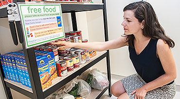 A volunteer stocks shelves in a food pantry for patients and families