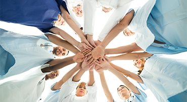 multiethnic medical team stacking hands over white background