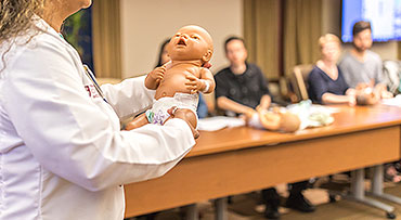 Nurse educator holds up an infant care demo doll in front of couples at a prenatal class
