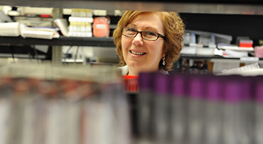 Portrait of physician Susana Marino, MD, PhD, D (ABHI), Associate Professor, Director, Transplant Immunology and Immunogenetics Lab, with an unidentified man in a lab