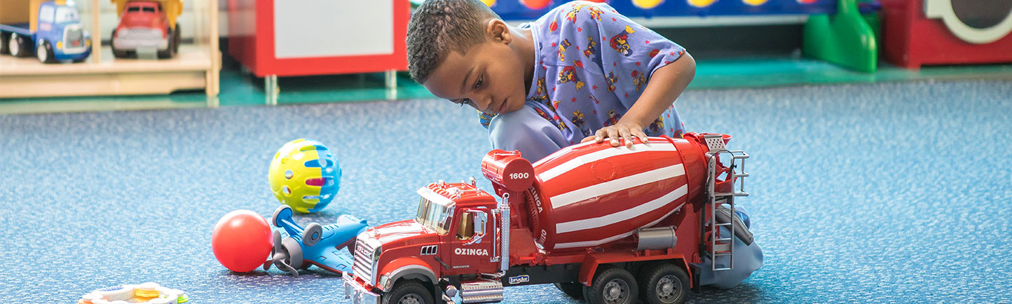 Comer patient playing with a fire truck in the playroom