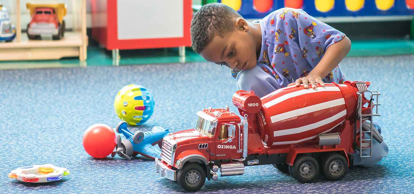 Pediatric hospital patient playing with a truck in the playroom
